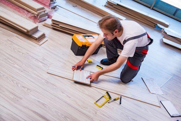 homem instalando piso vinílico em placa no chão